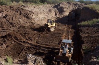 First phase of Construction - a bulldozer digs a base and into the sides of the riverbank to ancre the gabion